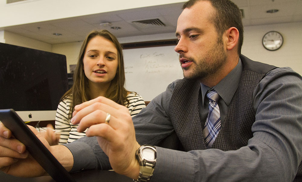 Assistant Professor of Interactive Media Steven King (right) critiques student Kate Weeks' application during the Mobile App Design and Development Class at at UNC Chapel Hill School of Journalism and Mass Communication.