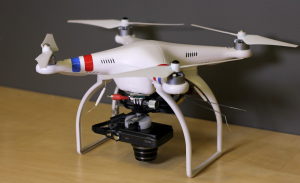 The drone-camera rig used to create the model of the dig site. A DJI Phantom 2 quad copter and a 12.1 megapixel Canon Powershot SX260 HS that has a built-in GPS chip that records the locations of each photograph.  Photo courtesy of the authors.